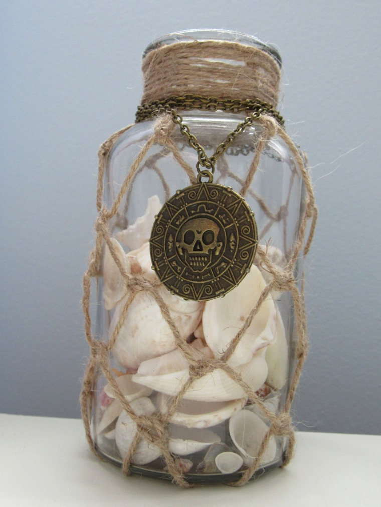 Vase, médaillon de pirate et coquillages